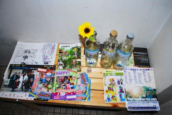 バーボンハウスさんの昇降階段の踊り場にあるテーブルに置かれたハッピー高円寺フライヤー、ボトル